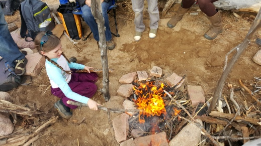 Andra tends the roaring fire!